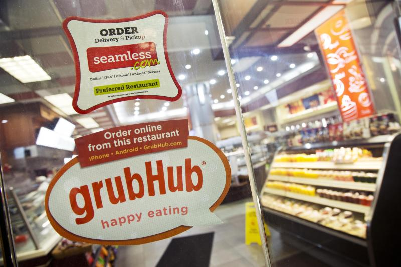FILE - This April 4, 2014 file photo shows signage for food delivery services GrubHub and Seamless displayed on the door of a restaurant in New York. The growing options for outsourcing meal planning, grocery shopping and cooking can be called time-saving blessings or culture-destroying curses. In the end, they're probably a complicated mix of both. (AP Photo/Mark Lennihan, File)
