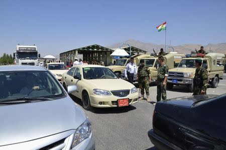 """Kurdish """"peshmerga"""" troops stand guard during an intensive security deployment at the checkpoint at the entrance to Sulaimaniya province August 8, 2014. REUTERS/Stringer"""