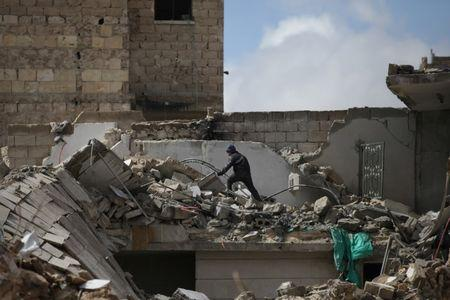 A boy walks over rubble of damaged buildings in the northern Syrian city of al-Bab