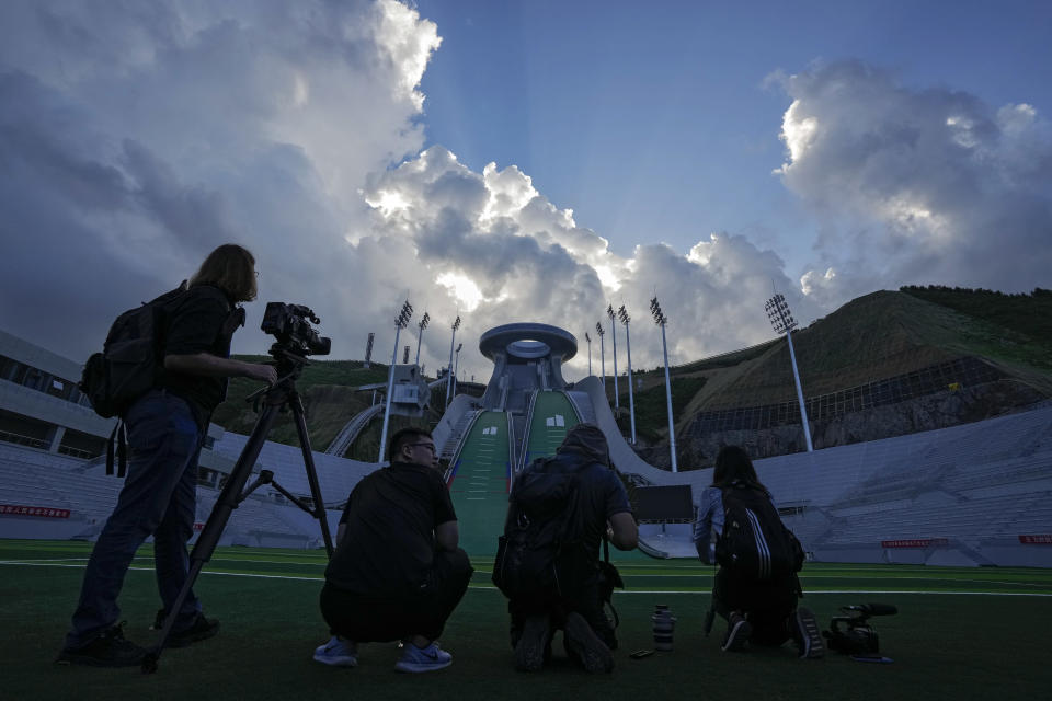FILE - In this July 14, 2021, file photo, journalists film the National Ski Jumping Centre, one of the venues for Beijing 2022 Olympic and Paralympic Winter Games, during a media tour in Zhangjiakou in northwestern China's Hebei province. The IOC says the Olympics are only about the sports; no politics allowed. But reporters from other countries who puncture the PR skin to explore other aspects of life in China — as they have in Japan during the Tokyo Olympics — could draw more than criticism. (AP Photo/Andy Wong, File)