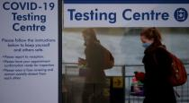 A passenger walks past a testing centre outside the terminal building of Manchester Airport amid the outbreak of the coronavirus disease (COVID-19) in Manchester