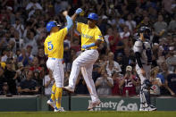 Boston Red Sox's Rafael Devers, center, celebrates with teammate Enrique Hernandez (5) after Hernandez scored on a three-run home run by Devers as New York Yankees catcher Kyle Higashioka, right, looks to the field during the sixth inning of a baseball game at Fenway Park, Friday, Sept. 24, 2021, in Boston. (AP Photo/Mary Schwalm)