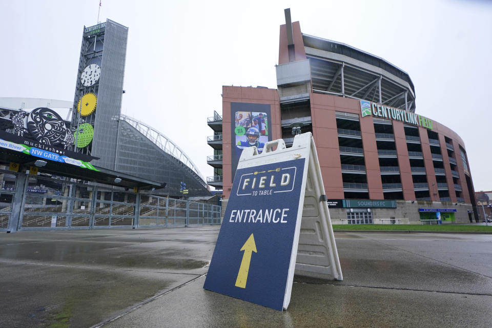 """A sign directs customers arriving for the """"Field To Table"""" event to an entrance at Lumen Field (formerly CenturyLink Field) the home of the Seattle Seahawks NFL football team, Thursday, Feb. 18, 2021, in Seattle. Thursday was the first night of several weeks of dates that offer four-course meals cooked by local chefs and served on the field at tables socially distanced as a precaution against the COVID-19 pandemic, which has severely limited options for dining out at restaurants in the area. (AP Photo/Ted S. Warren)"""