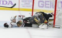 Chicago Blackhawks right wing Alex DeBrincat (12) falls into Vegas Golden Knights goaltender Marc-Andre Fleury (29) during the first period of an NHL hockey game Wednesday, Nov. 13, 2019, in Las Vegas. (AP Photo/John Locher)