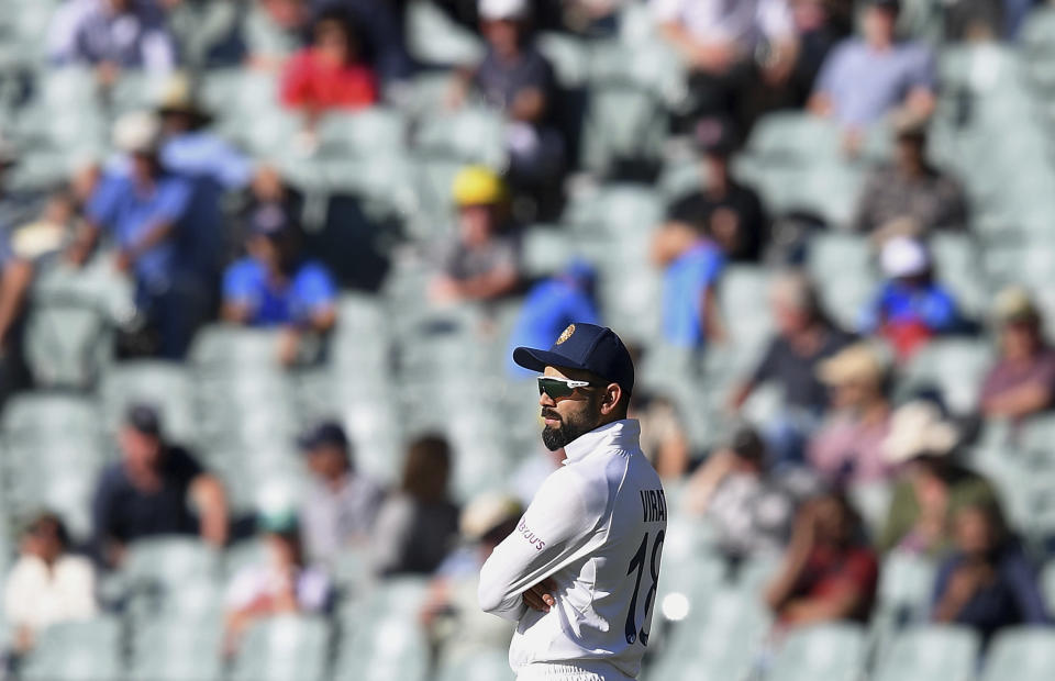 India's Virat Kohli stands with crossed arms near the end of their match against Australia on the third day of their cricket test match at the Adelaide Oval in Adelaide, Australia, Saturday, Dec. 19, 2020. Australia won the match. (AP Photo/David Mariuz)