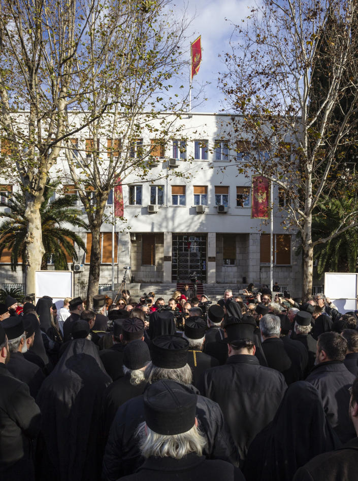Serbian Orthodox Church clergy in Montenegro gather in front of parliament building as they protest the planned adoption of a religious law that they say will pave the way to strip the church of its property, in Podgorica, Montenegro, Tuesday, Dec. 24, 2019. Montenegro's pro-Western president has accused the church of promoting pro-Serb policies in Montenegro and seeking to undermine the country's statehood since it split from Serbia in 2006. (AP Photo/Risto Bozovic)