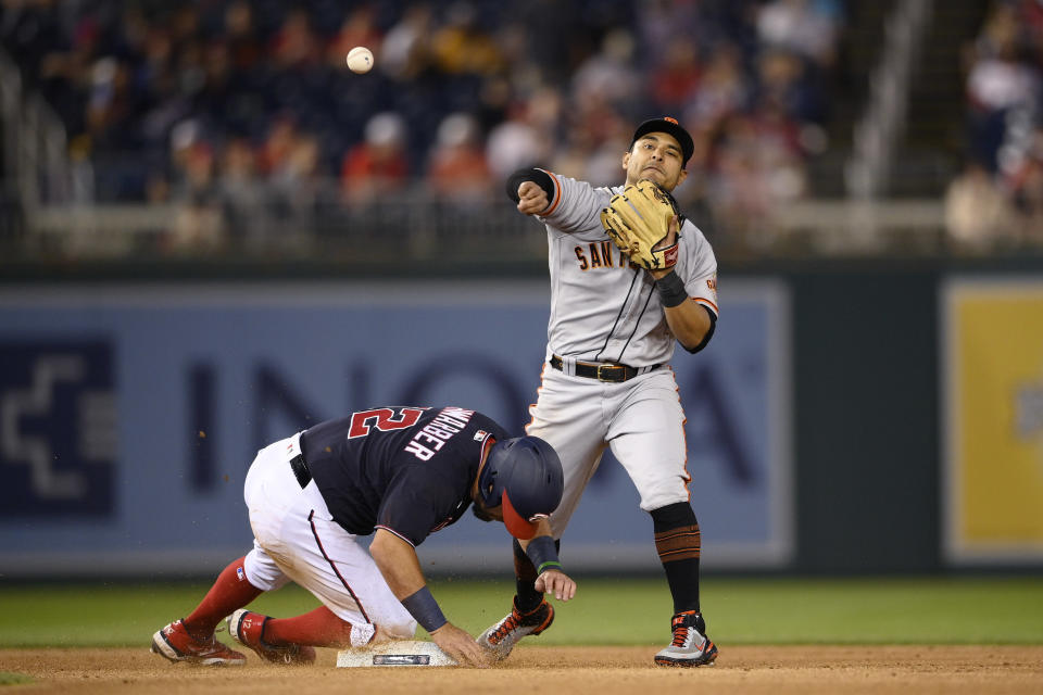 Washington Nationals' Kyle Schwarber (12) is out at second as San Francisco Giants second baseman Donovan Solano, right, throws to first to complete the double play on Yan Gomes during the fifth inning of a baseball game Friday, June 11, 2021, in Washington. (AP Photo/Nick Wass)
