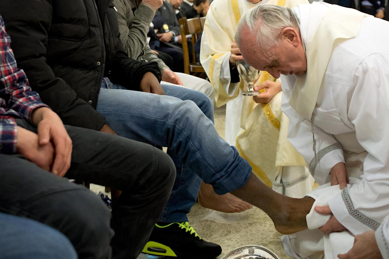 In this photo provided by the Vatican newspaper L'Osservatore Romano, Pope Francis washes the foot of an inmate at the juvenile detention center of Casal del Marmo, Rome, Thursday, March 28, 2013. Francis washed the feet of a dozen inmates at a juvenile detention center in a Holy Thursday ritual that he celebrated for years as archbishop and is continuing now that he is pope. Two of the 12 were young women, an unusual choice given that the rite re-enacts Jesus' washing of the feet of his male disciples. The Mass was held in the Casal del Marmo facility in Rome, where 46 young men and women currently are detained. Many of them are Gypsies or North African migrants, and the Vatican said the 12 selected for the rite weren't necessarily Catholic. (AP Photo/L'Osservatore Romano, ho)