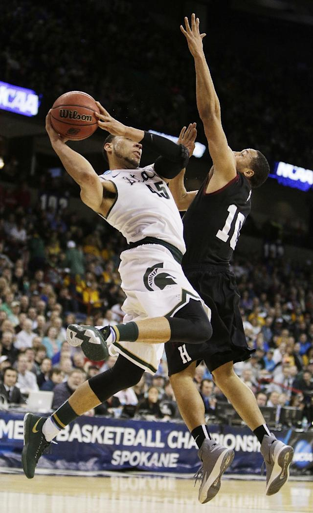 Michigan State's Denzel Valentine (45) passes the ball around Harvard's Brandyn Curry (10) in the first half during the third-round game of the NCAA men's college basketball tournament in Spokane, Wash., Saturday, March 22, 2014. (AP Photo/Young Kwak)