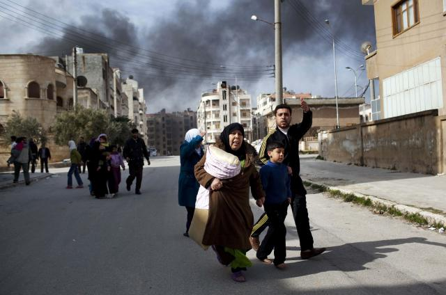 <p>A family escapes from fierce fighting between Free Syrian Army fighters and government troops in Idlib, north Syria, on March 10, 2012. This image was one in a series of 20 by AP photographers that won the 2013 Pulitzer Prize in Breaking News Photography. (Photo: Rodrigo Abd/AP) </p>