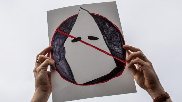 Joe Cook Gines holds an anti-Ku Klux Klan placard at Huntington Beach pier during an April protest against white supremacy in Huntington Beach, California. (Photo by Apu Gomes/Getty Images)