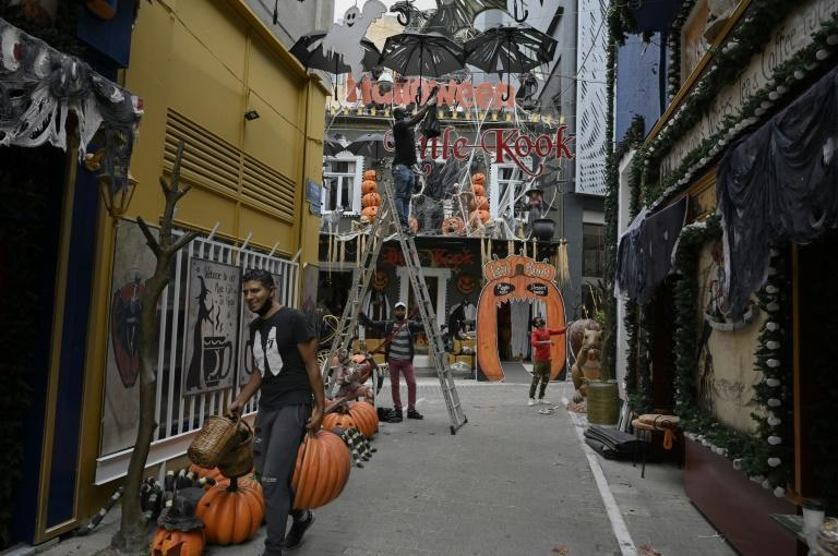 Workers remove halloween decorations from a thematic cafe in central Athens as cafes, bars, and restaurants closed due to partial lockdown to stem the spread of the novel coronavirus.