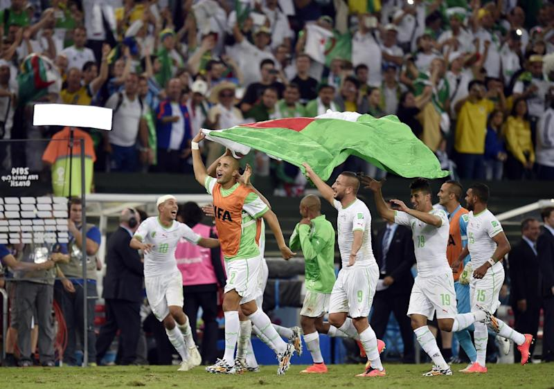 Algerian players celebrate after the group H World Cup soccer match between Algeria and Russia at the Arena da Baixada in Curitiba, Brazil, Thursday, June 26, 2014. The match ended in a 1-1 draw, but Algeria qualified for the round of 16