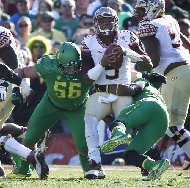 Florida State quarterback Jameis Winston, center, is tackled by Florida State linebacker Novisa Petrusich, left, and defensive tackle Arthur Williams during the first half of the Rose Bowl NCAA college football playoff semifinal, Thursday, Jan. 1, 2015, in Pasadena, Calif. (AP Photo/Lenny Ignelzi)