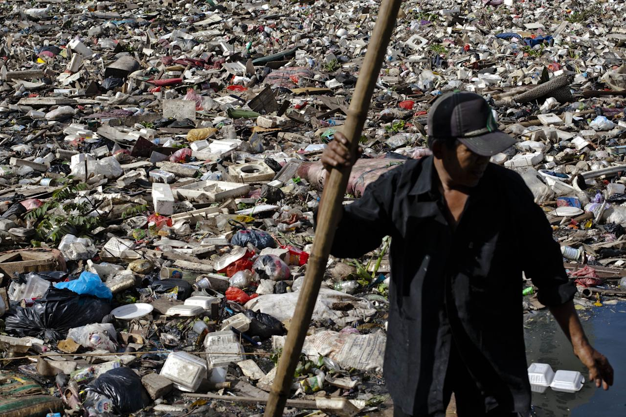 JAKARTA, INDONESIA - JANUARY 26:  A worker cleans up waste that was piled up by the flood at Pakin river in North Jakarta on January 26, 2013 in Jakarta, Indonesia. With heavy rain forecast for January 26-28, Indonesian authorities have organised the use of generators and cloud-seeding measures to defuse rain-laden clouds to help prevent further flooding of Jakarta, following last week's floods which claimed the lives of 32 people.  (Photo by Ulet Ifansasti/Getty Images)