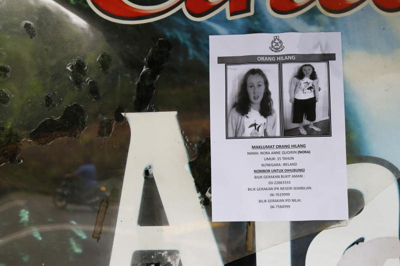 A poster of a missing British girl Nora Anne Quoirin is seen as a motorcyclist, reflected on a acrylic, rides past in Seremban, Negeri Sembilan, Malaysia, Saturday, Aug. 10, 2019. The parents of the 15-year-old London girl who mysteriously disappeared from a Malaysian resort a week ago said Saturday that she wasn't independent and had difficulty walking, in new details to support their conviction that she was abducted. (AP Photo/Lai Seng Sin)