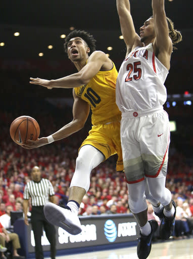 California forward Justice Sueing (10) drives past Arizona forward Keanu Pinder during the first half during an NCAA college basketball game Saturday, March 3, 2018, in Tucson, Ariz. (AP Photo/Rick Scuteri)