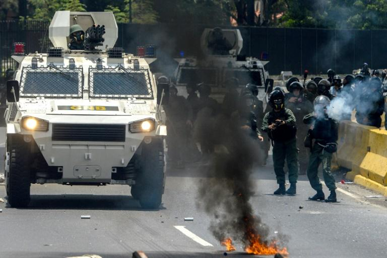 Venezuelan National Guard personnel in riot gear and opposition activists clash in Caracas on April 10, 2017
