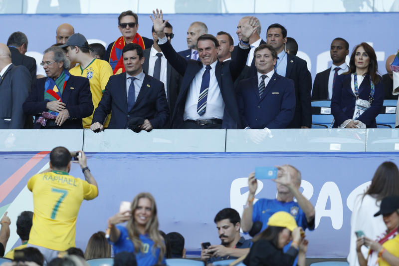 Brazil's President Jair Bolsonaro, top center, gestures next Brazil's Justice Minister Sergio Moro, center left, and Conmebol President Alejandro Dominguez, center right, prior to the final soccer match of the Copa America between Brazil and Peru at the Maracana stadium in Rio de Janeiro, Brazil, Sunday, July 7, 2019. (AP Photo/Victor R. Caivano)