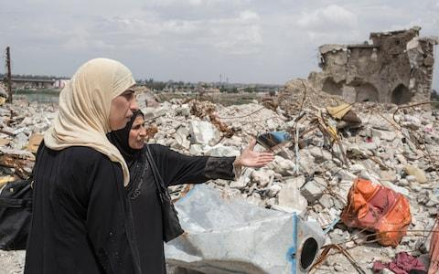 Byda'a Thanoon, 47, and sister Khawla Thanoon, 57, look for where their mother may be buried under the rubble near their destroyed house in the old city of Mosul - Credit: Sam Tarling for The Telegraph