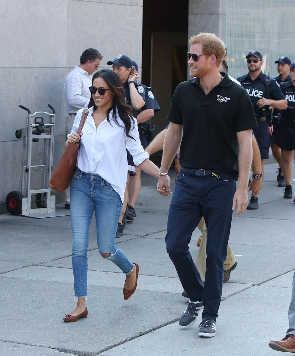 """<p>Markle made an adorable appearance with Prince Harry <a href=""""https://www.townandcountrymag.com/society/tradition/a12466469/meghan-markle-prince-harry-hold-hands-invictus-games/"""" rel=""""nofollow noopener"""" target=""""_blank"""" data-ylk=""""slk:(please note the hand-holding!)"""" class=""""link rapid-noclick-resp"""">(please note the hand-holding!)</a> while in Toronto for the Invictus Games. Markle kept it casual in ripped light wash jeans and a white button down shirt, complete with a brown bag and <a href=""""https://go.redirectingat.com?id=74968X1596630&url=https%3A%2F%2Fwww.sarahflint.com%2Fproducts%2Fnatalie-saddle-vachetta%3Fvariant%3D4419256188958&sref=https%3A%2F%2Fwww.townandcountrymag.com%2Fstyle%2Ffashion-trends%2Fg3272%2Fmeghan-markle-preppy-style%2F"""" rel=""""nofollow noopener"""" target=""""_blank"""" data-ylk=""""slk:brown flats from Sarah Flint"""" class=""""link rapid-noclick-resp"""">brown flats from Sarah Flint</a>. </p><p><strong>More</strong>: <a href=""""https://www.townandcountrymag.com/style/a12467025/meghan-markle-shoes-sarah-flint/"""" rel=""""nofollow noopener"""" target=""""_blank"""" data-ylk=""""slk:Here's Where You Can Buy Meghan Markle's Sarah Flint &quot;Natalie&quot; Flats"""" class=""""link rapid-noclick-resp"""">Here's Where You Can Buy Meghan Markle's Sarah Flint """"Natalie"""" Flats</a><br></p>"""