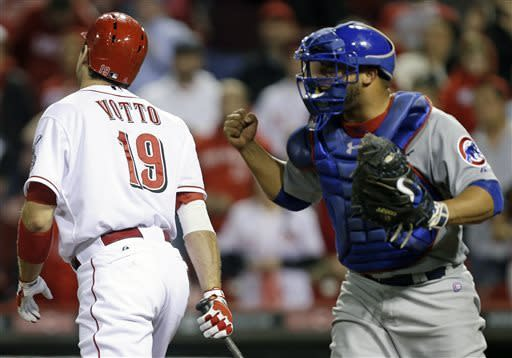 Chicago Cubs catcher Welington Castillo clinches his fist as Cincinnati Reds' Joey Votto (19) strikes out against relief pitcher Kevin Gregg to end their 10-inning baseball game, Tuesday, April 23, 2013, in Cincinnati. Chicago won 4-2. (AP Photo/Al Behrman)