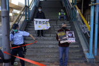 Pro-democracy activists, including Lee Cheuk-Yan, right, hold placards with the picture of the Chinese citizen journalist Zhang Zhan as they march to the Chinese central government's liaison office, in Hong Kong, Monday, Dec. 28, 2020. They demanded the release of the 12 Hong Kong activists detained at sea by Chinese authorities. (AP Photo/Kin Cheung)