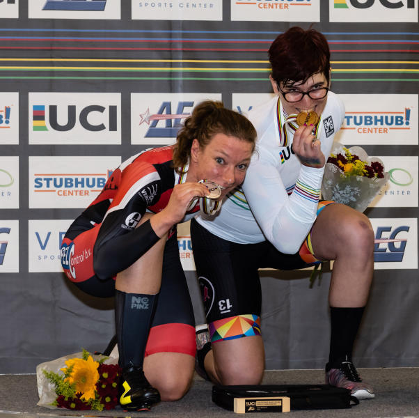 In this Oct. 13, 2018 photo provided by Craig Huffman, transgender cyclist Rachel McKinnon of Canada, right, bites her gold medal with silver medalist Carolien Van Herrikhuyzen of the Netherlands during the UCI Masters Track Cycling World Championships in Carson, Calif. Initially, McKinnon was elated with her win, even though one of her top rivals pulled out of the final at the last minute. But there quickly was a downside to the victory, as a photo gained attention across the internet showing her on the podium with the two smaller, skinnier runners-up. (Craig Huffman/Craig Huffman Photography via AP)