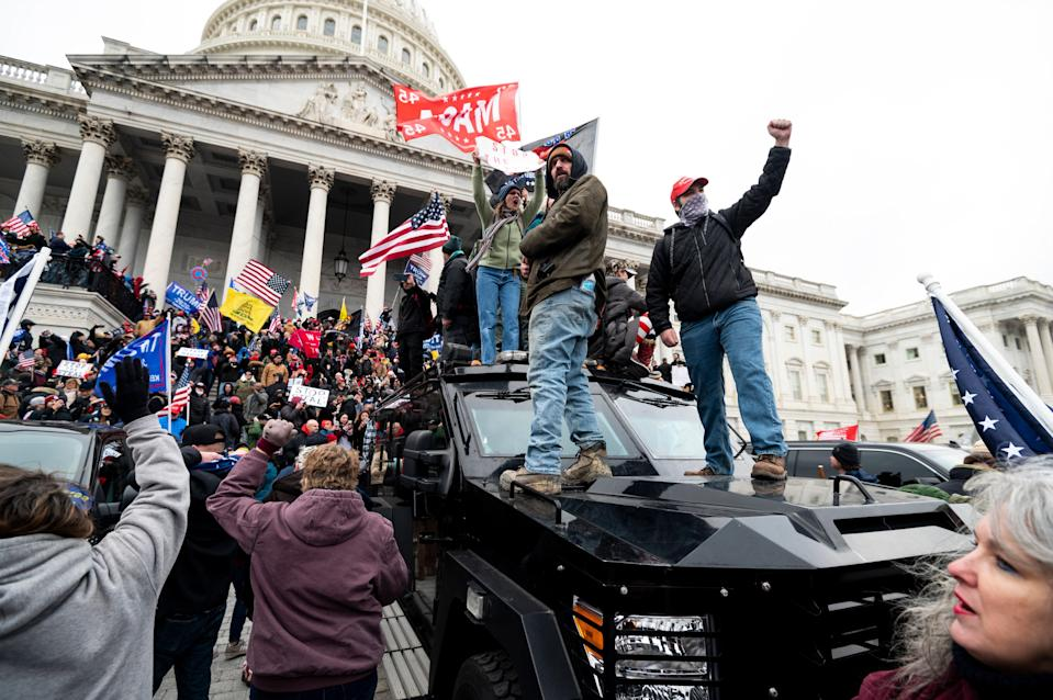 Trump supporters stand on a U.S. Capitol Police armored vehicle as others take over the steps of the Capitol.