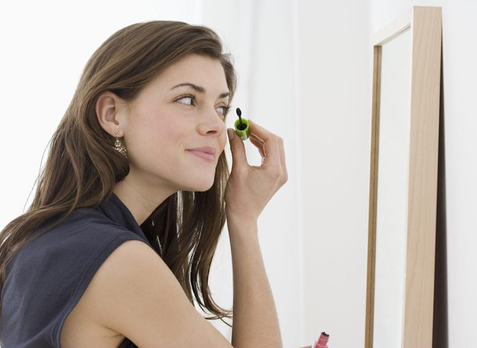 Young woman applying mascara in mirror, smiling