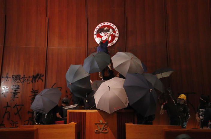 Protesters deface the Hong Kong logo at the Legislative Council to protest against the extradition bill in Hong Kong, Monday, July 1, 2019. (Photo: Vincent Yu/AP)
