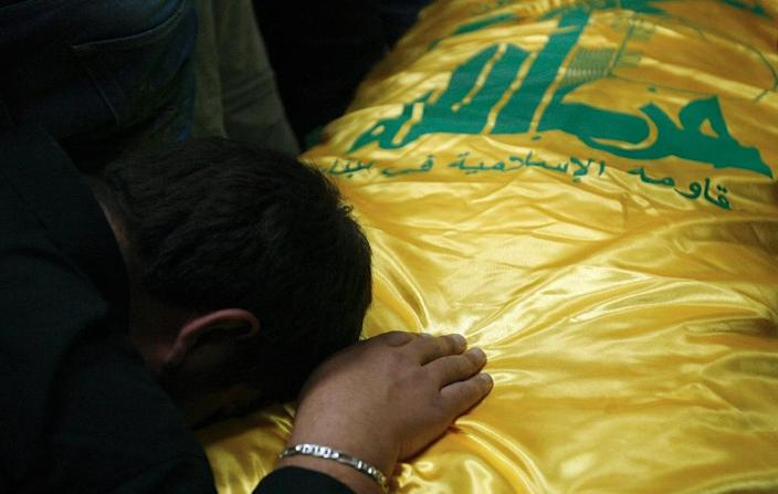 A Lebanese man mourns over the coffin of a Hezbollah militant who was killed whilst fighting Syrian rebels in the Qalamun region, during his funeral in the southern Lebanese city of Sidon, on May 14, 2015 (AFP Photo/Mahmoud Zayyat)