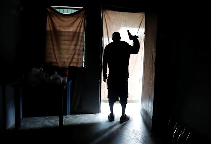 An MS-13 gang member looks out from a house as police patrol the street in San Pedro Sula, Honduras, in September. He was later injured during a gang shootout and died of his injuries, according to a police report. (Photo: Goran Tomasevic/Reuters)
