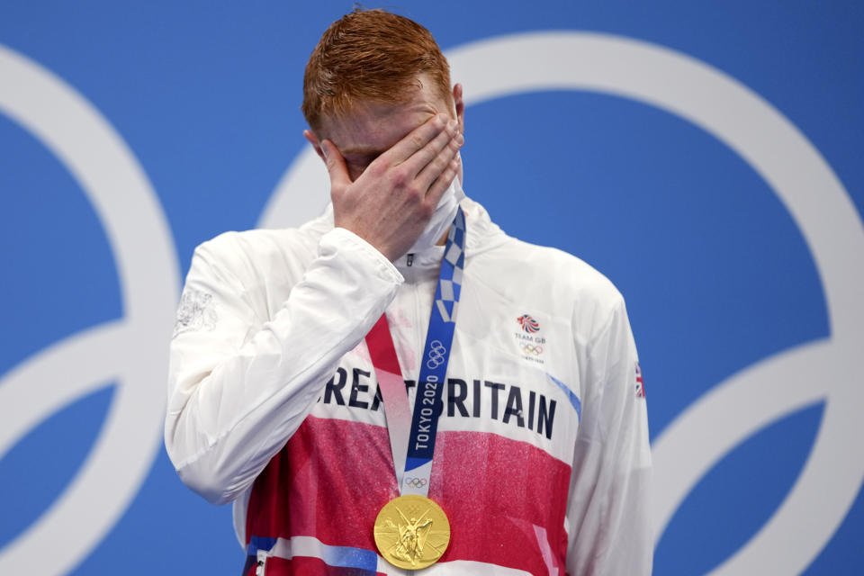 Tom Dean of Britain covers his face after receiving his gold medal on the podium after winning the men's 200-meter freestyle at the 2020 Summer Olympics, Tuesday, July 27, 2021, in Tokyo, Japan. (AP Photo/Matthias Schrader)