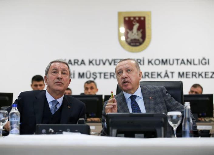 FILE PHOTO: Turkish President Tayyip Erdogan and Defence Minister Hulusi Akar attend a briefing at the Land Forces' Forward Joint Operation Command Center in Sanlıurfa