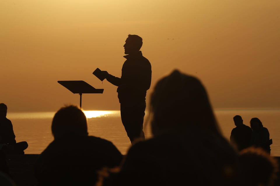 Park Community Church Associate Pastor Trevor Lovell is silhouetted against the sky as he leads an Easter sunrise service while parishioners listen on Sunday, April 4, 2021, at North Avenue Beach in Chicago. (AP Photo/Shafkat Anowar)