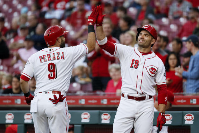 Cincinnati Reds' Jose Peraza (9) celebrates with Joey Votto (19) after hitting a solo home run off Kansas City Royals starting pitcher Heath Fillmyer during the first inning of a baseball game Wednesday, Sept. 26, 2018, in Cincinnati. (AP Photo/John Minchillo)