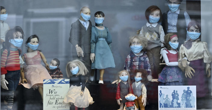 The puppet theatre characters wear masks in the display window of the Waidspeicher theatre in Erfurt, Germany, Tuesday, Jan. 5, 2021. Citizens in Germany will probably have to prepare for further restrictions in order to significantly reduce the number of Corona infections. This is becoming apparent ahead of new consultations between the federal and state governments. (Martin Schutt/dpa via AP)
