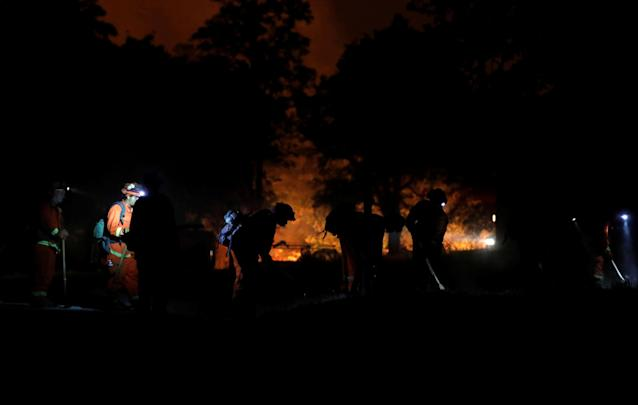 <p>Inmate fire crews cut a fire line during the evening as crews battle the Carr Fire, west of Redding, Calif., July 27, 2018. (Photo: Fred Greaves/Reuters) </p>