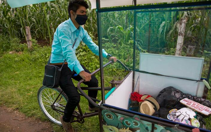 Teacher Gerardo Ixcoy pedals his adult tricycle converted into a mobile classroom past cornfields, in Guatemala. The 27-year-old invested his savings in the classroom-on-a-trike in order to give individual instruction to his sixth-grade students - AP