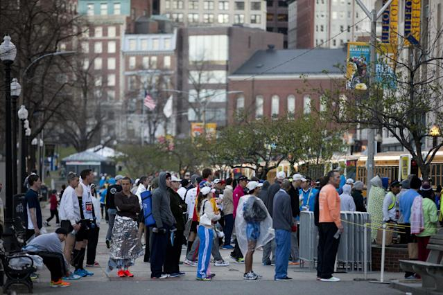 Runners cue to board busses ahead of the 118th Boston Marathon Monday, April 21, 2014 in Boston. (AP Photo/Matt Rourke)