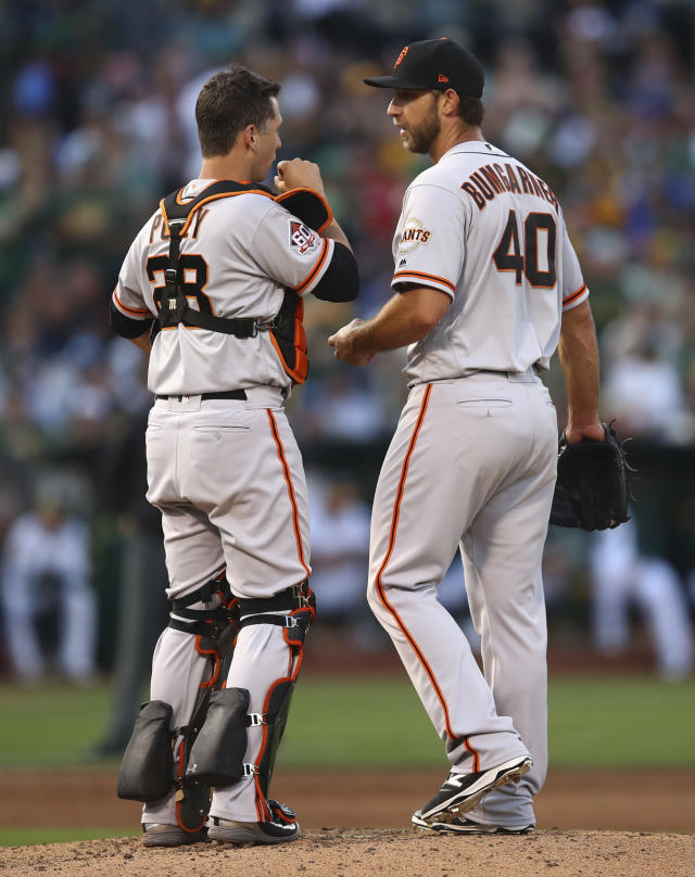San Francisco Giants pitcher Madison Bumgarner, right, meets with Buster Posey in the fifth inning of a baseball game against the Oakland Athletics Saturday, July 21, 2018, in Oakland, Calif. (AP Photo/Ben Margot)