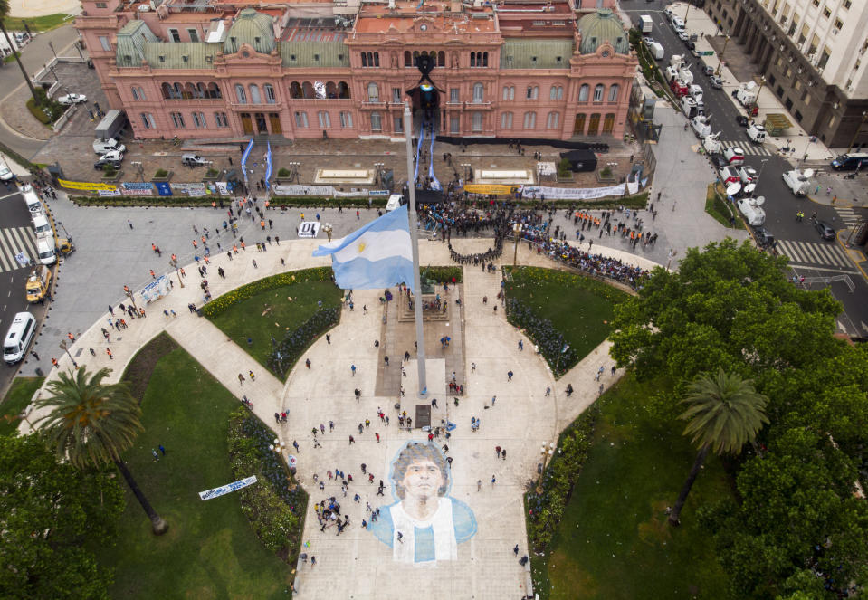 People line up to attend the wake of Diego Maradona at the presidential palace in Buenos Aires, Argentina, Thursday, Nov. 26, 2020. The Argentine soccer great who led his country to the 1986 World Cup title died Wednesday at the age of 60. (AP Photo/Mario De Fina)