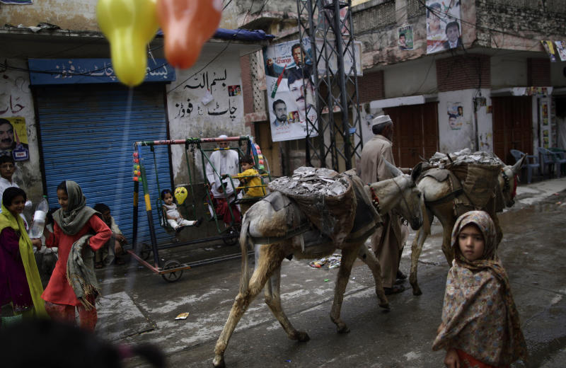 With election banners showing cricket star-turned-politician, and leader of Pakistan Tehreek-e-Insaf party, Imran Khan, and other member of his party, a Pakistani daily laborer walks his donkeys past children playing in a neighborhood in Rawalpindi, Pakistan, Sunday, May 12, 2013. Pakistan's former prime minister Nawaz Sharif looked set Sunday to return to power for a third term, with an overwhelming election tally that just weeks ago seemed out of reach for a man who had been ousted by a coup and was exiled abroad before clawing his way back as an opposition leader. (AP Photo/Muhammed Muheisen)