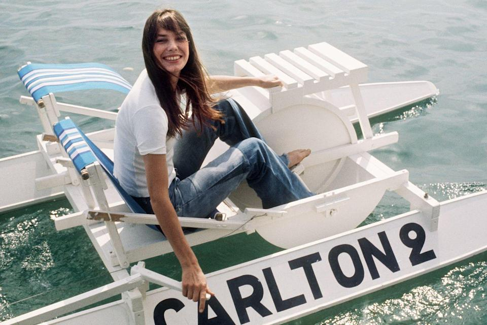 <p>Jane Birkin dresses casually in a white T-shirt and jeans for a day on a pedal boat in 1974. </p>