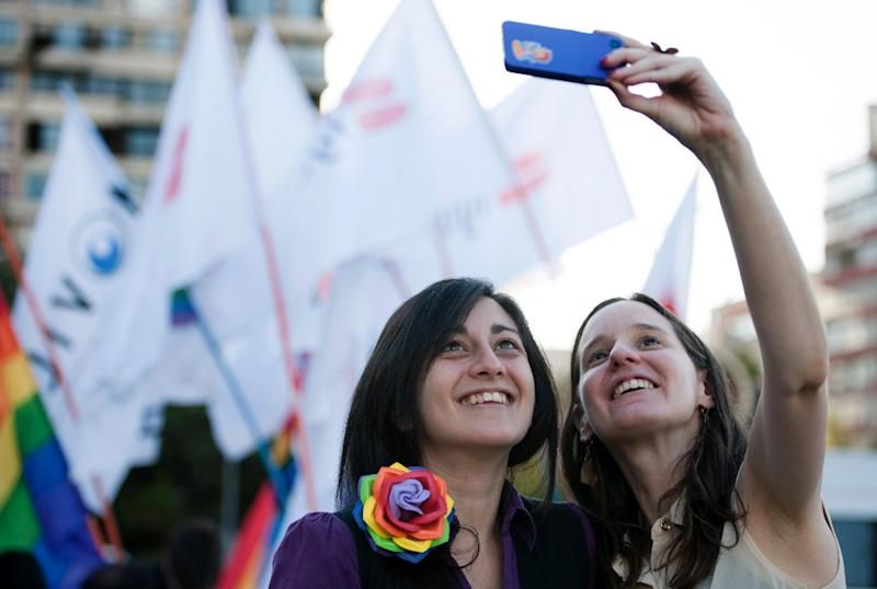 A couple takes a selfie during the celebration of the approval of the first law that would allow same-sex couples to enter into civil unions in Santiago on January 28, 2015