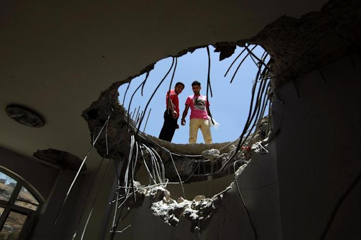 Yemenis look through a hole in the roof of a house which was damaged the day before during an air strike by Saudi-led coalition warplanes on the nearby base on Fajj Attan hill on April 21, 2015 in the capital Sanaa (AFP Photo/Mohammed Huwais)