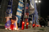 Candles lie next to a picture of Diego Armando Maradona outside the San Paolo Stadium to pay their homage to the late soccer legend, in Naples, Italy, Wednesday, Nov. 25, 2020. Diego Maradona has died. The Argentine soccer great was among the best players ever and who led his country to the 1986 World Cup title before later struggling with cocaine use and obesity. He was 60. (AP Photo/Alessandra Tarantino)