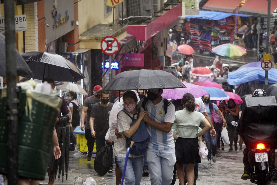 Pedestrians walk on a rainy day through the streets of São Paulo, Brazil, on January 12, 2021. (Photo by Cris Faga/NurPhoto via Getty Images)