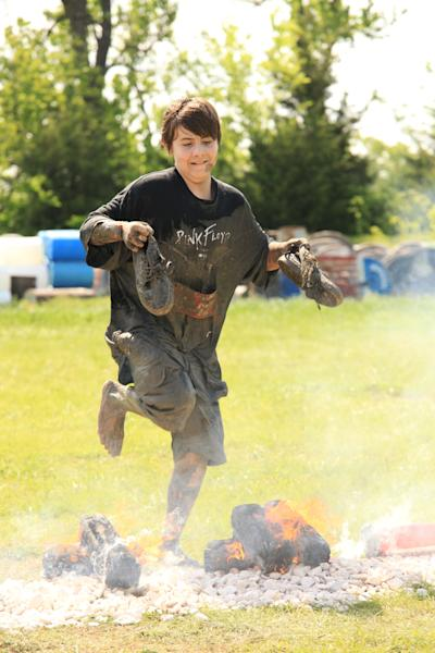 This Saturday, April 27, 2013 photo provided by Nuvision Action Image LLC shows a contestant in the Fire Jump competing during The Survival Race in Dallas. (AP Photo/Nuvision Action Image LLC)